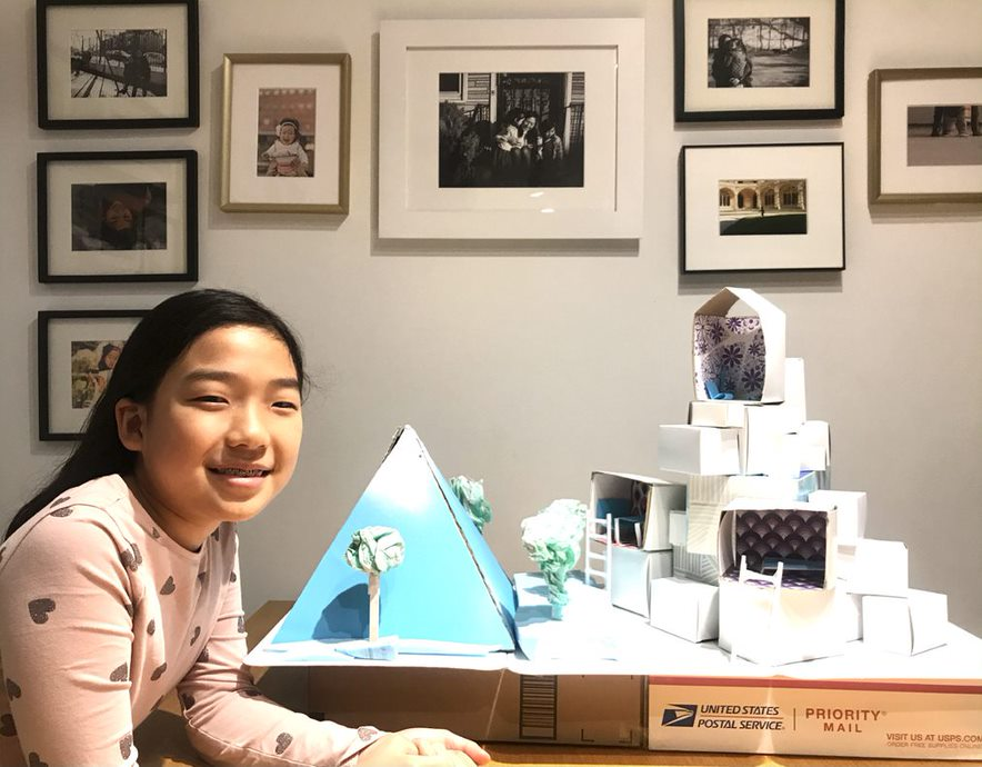 Child posing with pyramid and building model